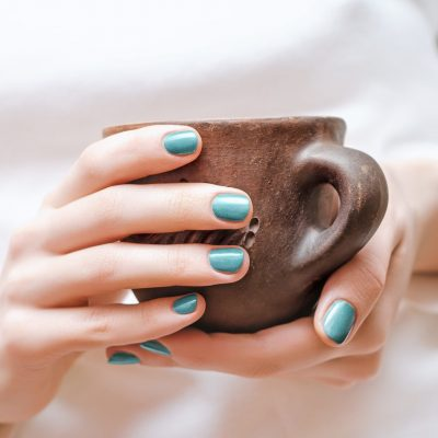 Female hands with green nail design holding a cup.